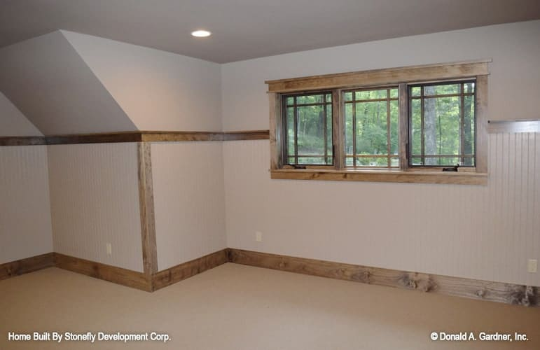 Spacious bonus room with triple panel windows, carpet flooring, and beige walls lined with wooden trims.