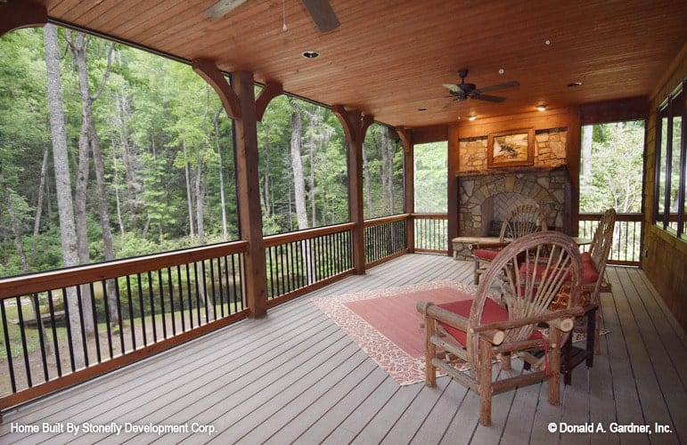 The screened porch is filled with a fireplace alcove, cushioned chairs, ceiling fans, and a red bordered rug that lays on the wide plank flooring.