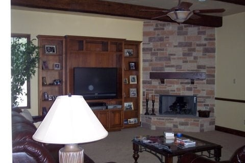 The den has leather seats, a glass top coffee table, a wall-mounted TV, and a corner brick fireplace.