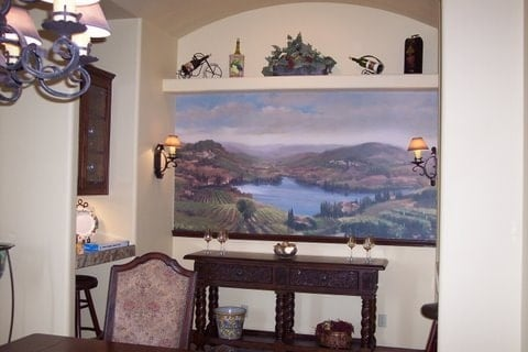 Dining area with a wooden buffet table, built-in desk, and a large landscape painting adorning the beige wall.