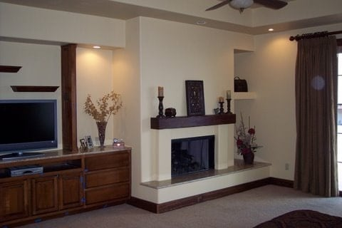 The living room showcases a wooden built-in, flatscreen TV, and a cozy fireplace.