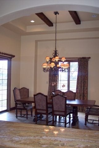 Dining room with cushioned chairs, a rectangular dining table, and an ornate chandelier that hangs from the beamed ceiling.