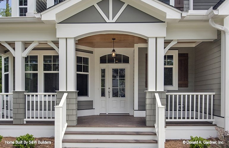 Front porch with white railings, double columns, and a wooden stoop.