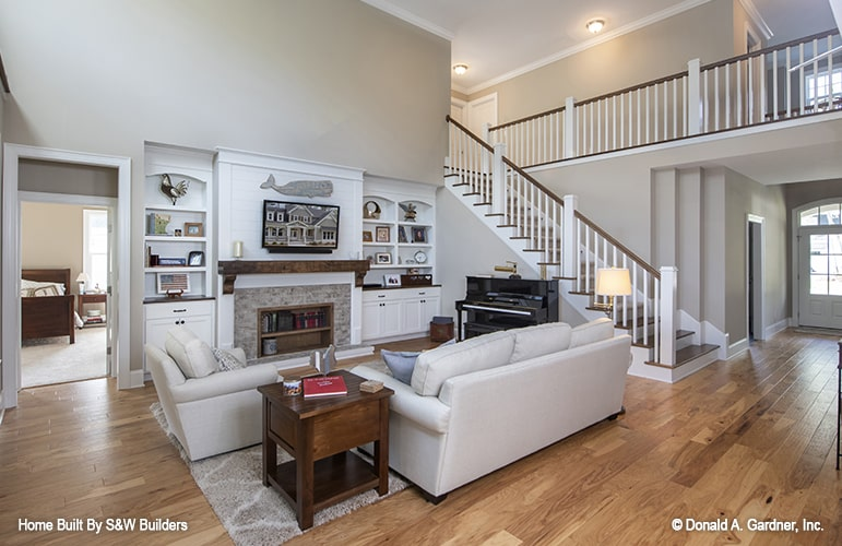 Great room with gray sofas, wooden tables, white built-ins, and an upright piano.