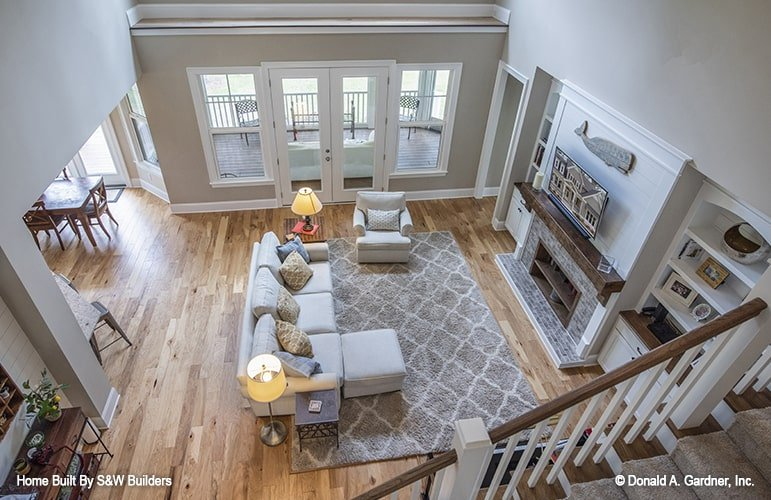 View of the living room from the second-floor balcony showing the hardwood flooring and a french door that opens out to the screened porch.