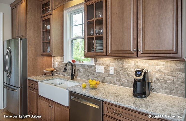 Kitchen with wooden cabinets, a farmhouse sink, slate appliances, and granite countertop.