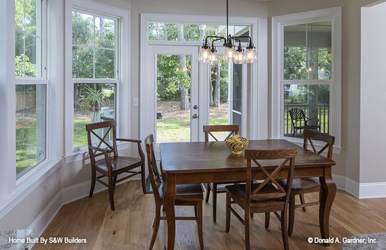 Breakfast room with wooden dining table, matching chairs, and a wrought iron chandelier.