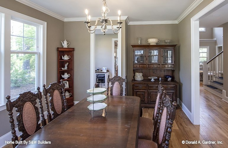 The dining room offers a display cabinet, corner shelving unit, and a rectangular dining set well-lit by a candle chandelier.