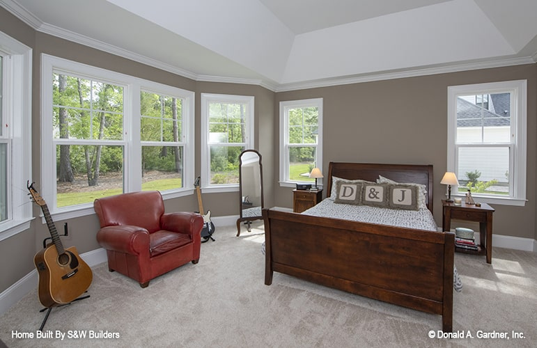 Primary bedroom with a coved ceiling, carpet flooring, wooden bed, red leather armchair, and a full-length mirror.