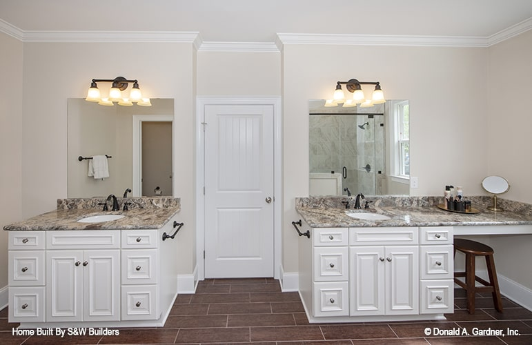 Warm glass sconces illuminate the two vanities with frameless mirrors.