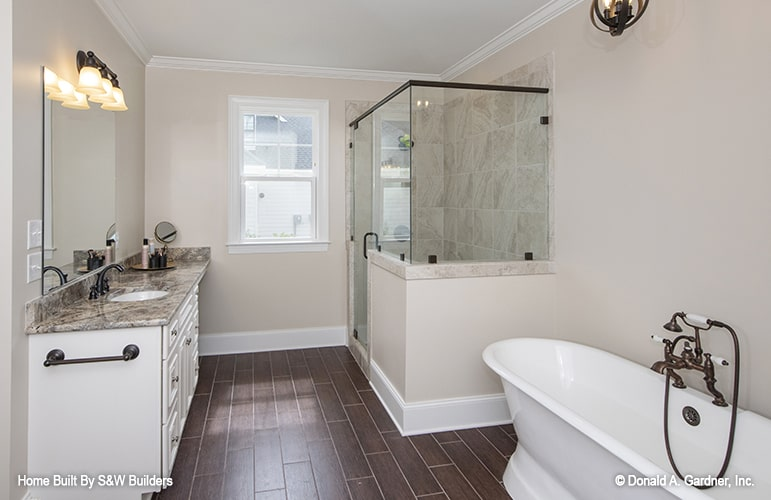 The primary bathroom is equipped with a granite top vanity, walk-in shower, and a freestanding bathtub.