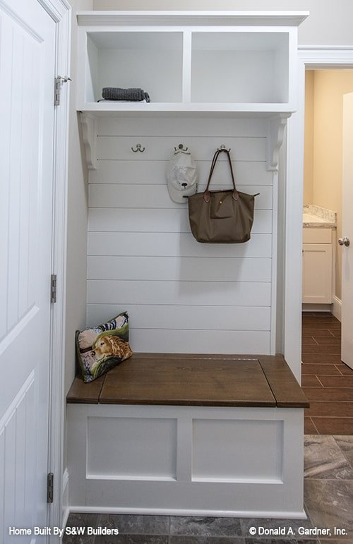 Mudroom with built-in shelves, storage bench, and bag hooks.