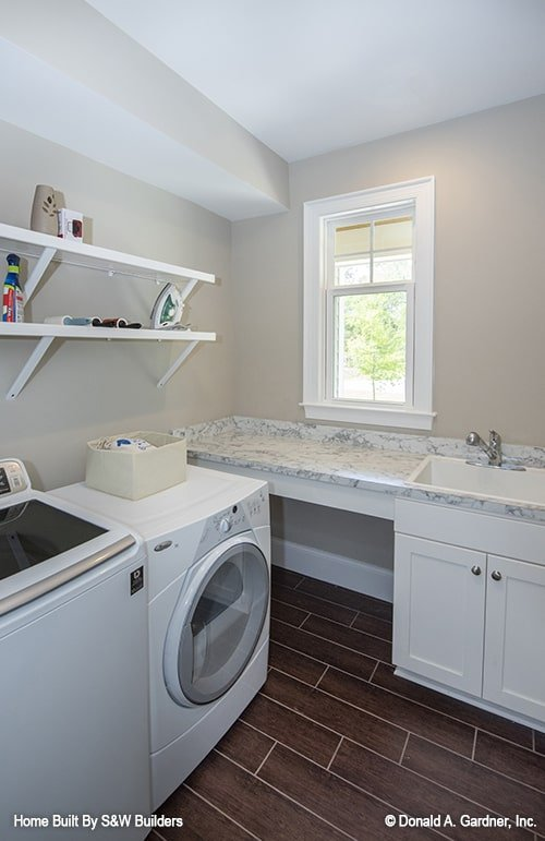 Utility with white appliances, porcelain sink, floating shelves, and wide plank flooring.
