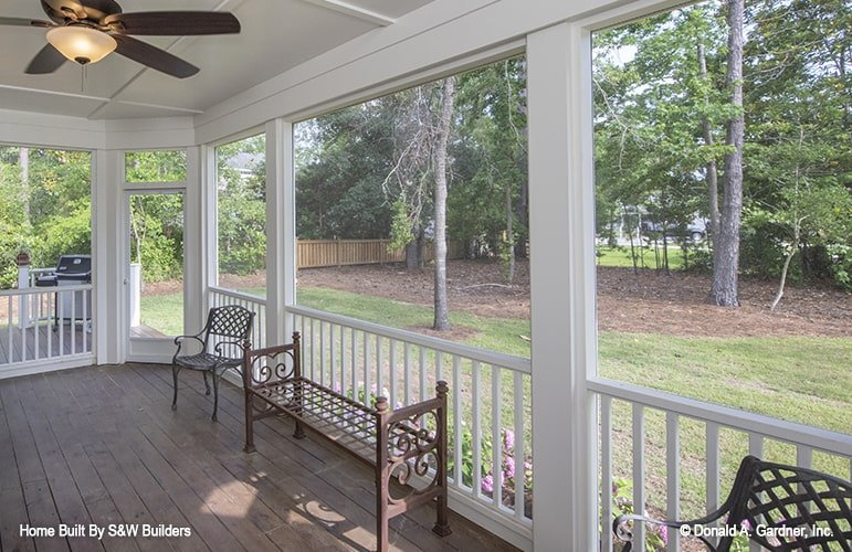 Screened porch with ornate chairs and bench, white railings, and a traditional fan mounted on the paneled ceiling.