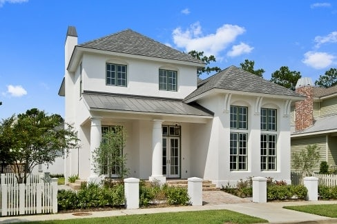 Front exterior view showing the stucco siding, white french doors, and a covered porch lined with large columns.