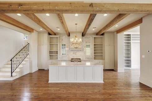 The kitchen has a beamed ceiling, white cabinets, and a marble top island lit by a candle chandelier.