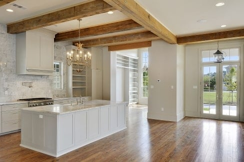 An angled view shows the kitchen and foyer that features a french entry door.
