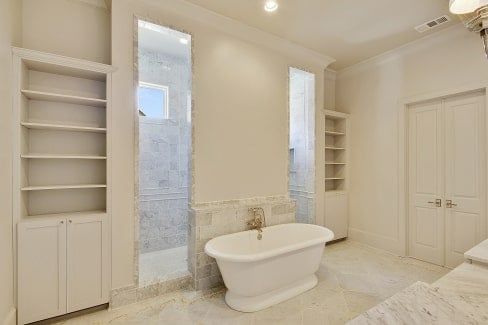 The primary bath is equipped with marble top vanity, white built-ins, a freestanding tub, and a spacious walk-in shower.