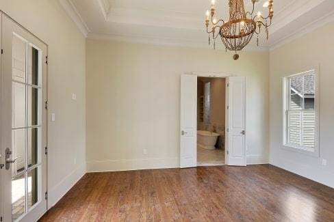 Primary suite with hardwood flooring and a tray ceiling mounted with a beaded chandelier.