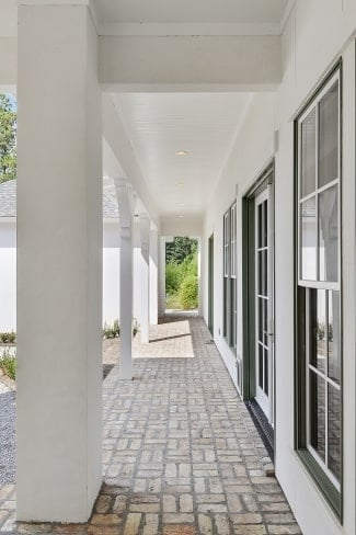 Covered porch with brick flooring and large columns that blend with the white ceiling.
