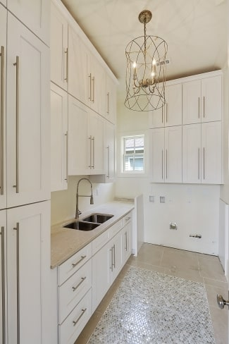 The utility room is filled with white modular cabinets, a double bowl sink, and a cylindrical chandelier.