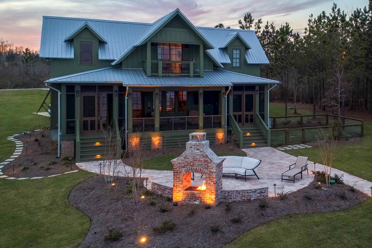 Rear view during sunset showing the warm glow from the outdoor lamps and fireplace.