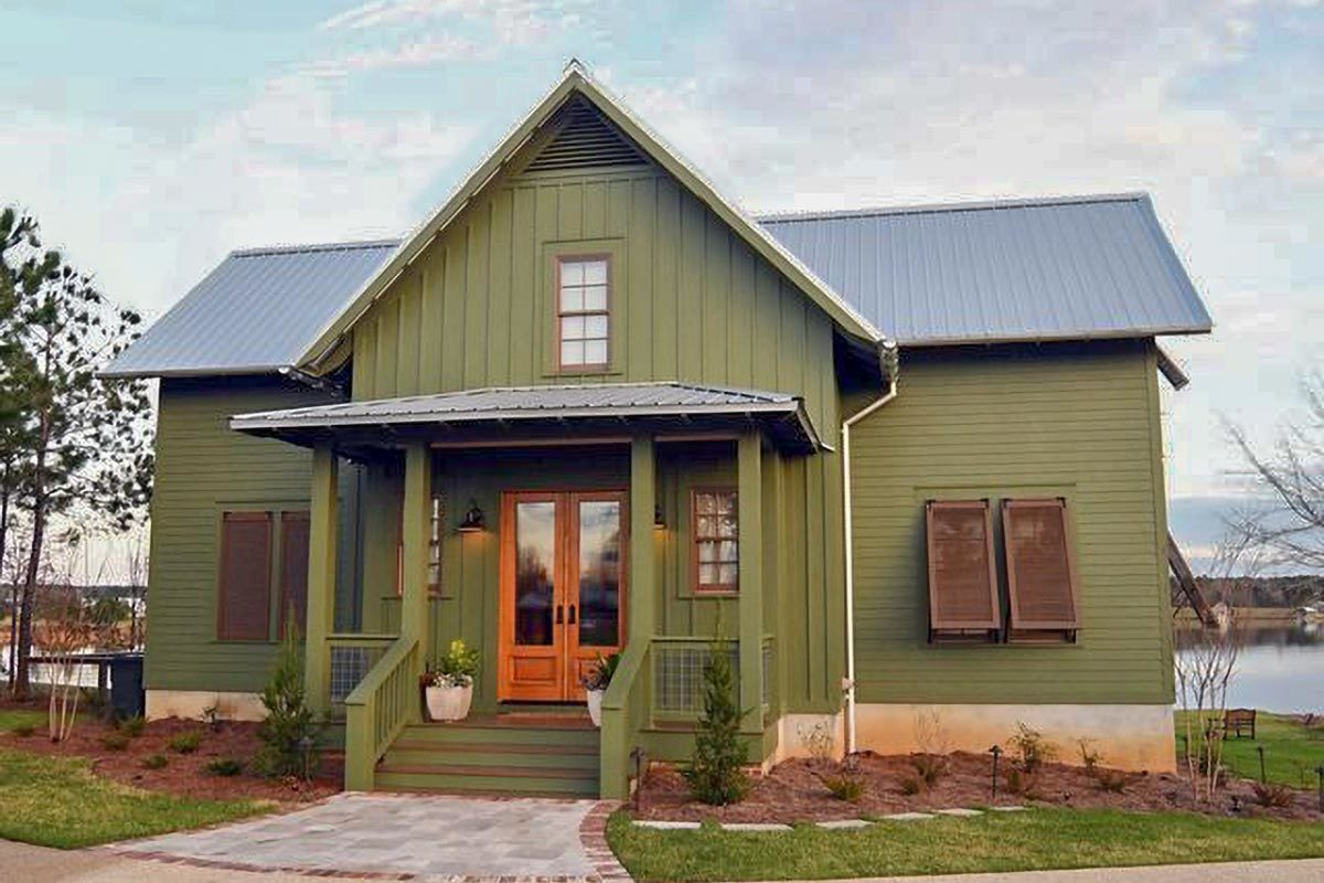 Front exterior view with a board and batten green siding and a covered porch with a french entry door.
