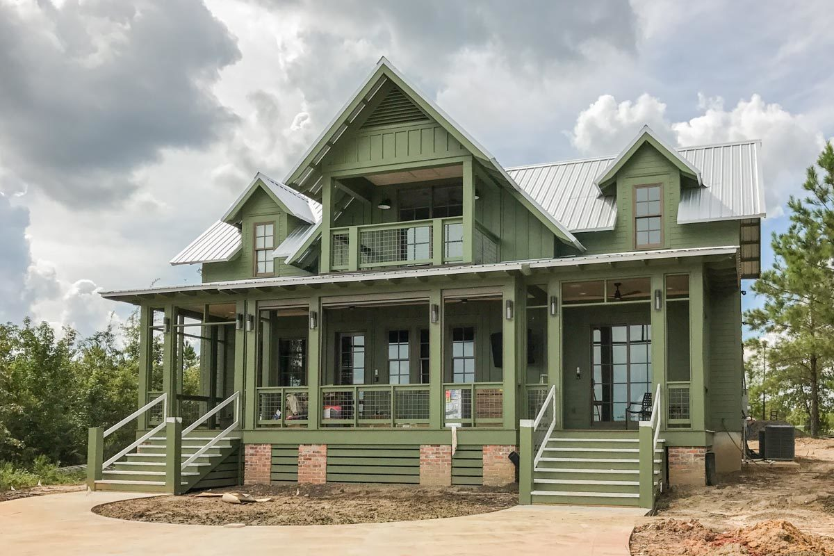 Double staircase and green columns frame the rear covered porch.