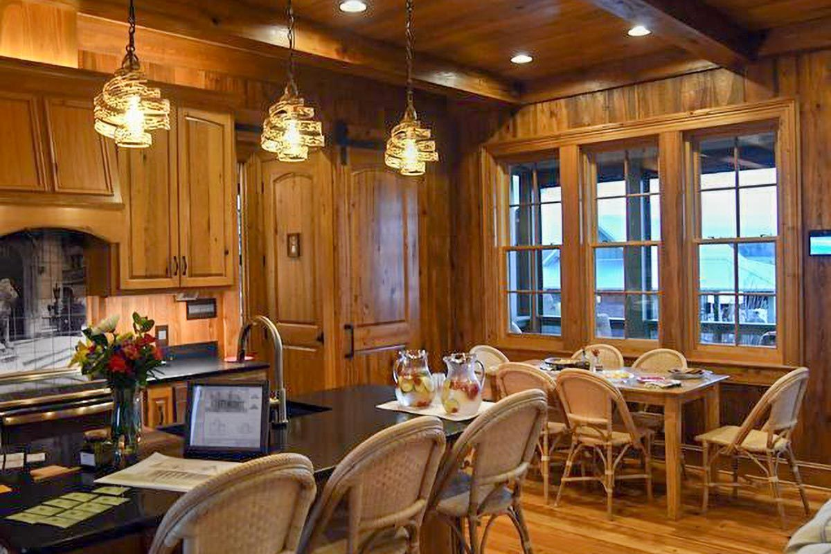 The dining area offers round back chairs and a rectangular dining table that blends in with the hardwood flooring.