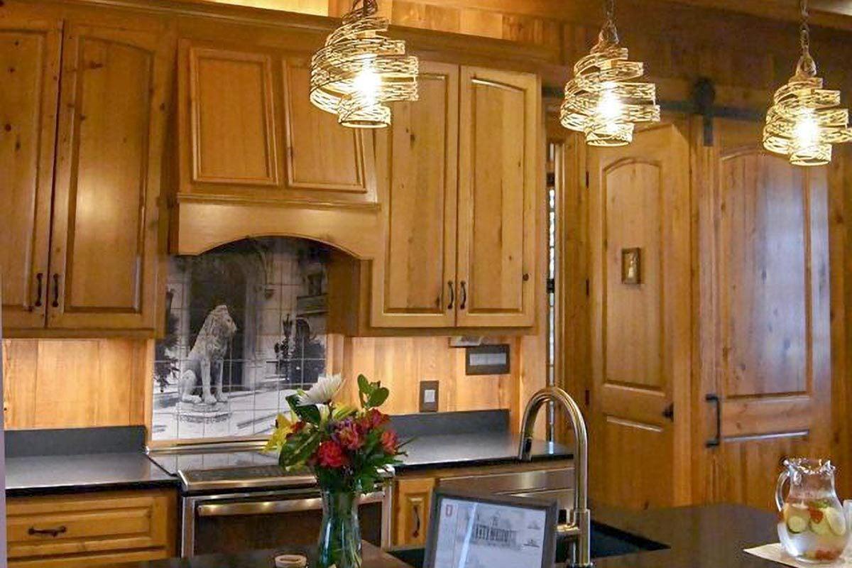 Kitchen with wooden cabinetry, black granite countertops, decorative tile backsplash, stylish glass pendants, and a prep island.