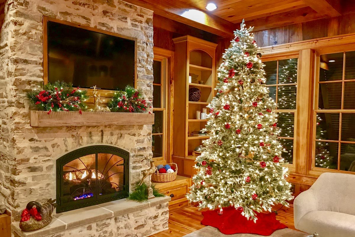 Tall Chrismas tree and decors adorn the stone fireplace that's topped with a wall-mounted TV.
