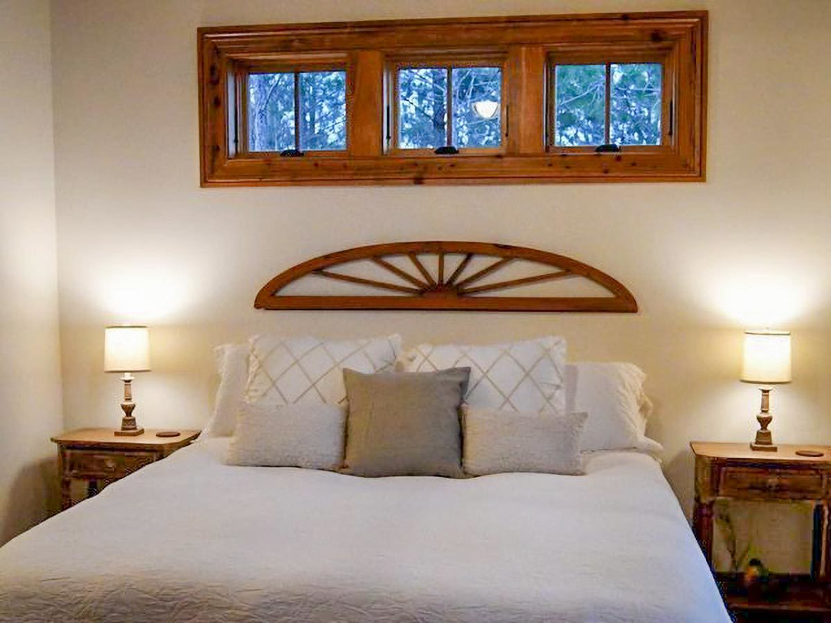 Wooden nightstands and table lamps flank the cozy bed that's placed under the three-panel window.