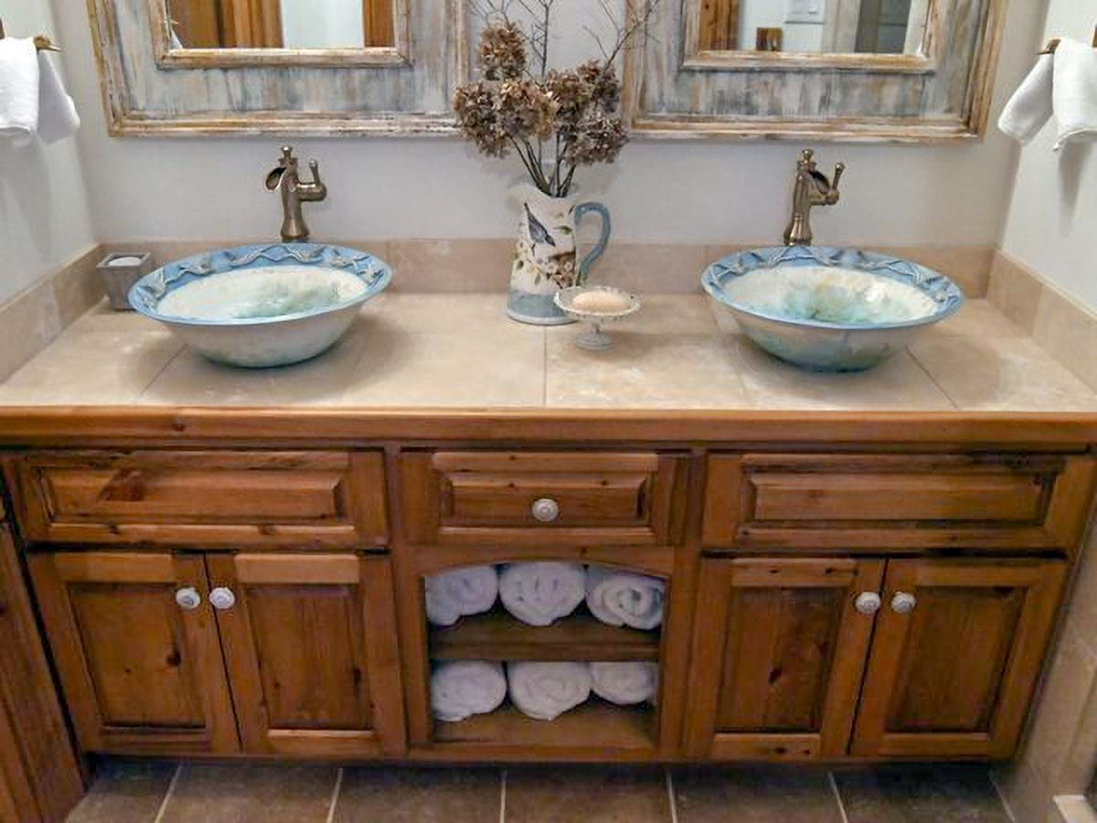 This bathroom has a wooden vanity with a granite countertop, decorative vessel sinks, and a pair of distressed mirrors.