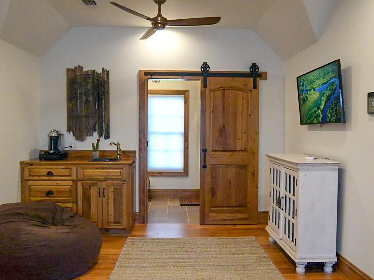 A wooden barn door opens to this vaulted room filled with cabinets, a sink, TV, bean bag, and an area tug that lays on the hardwood flooring.