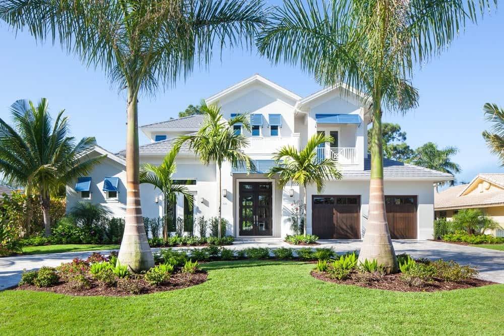 Front exterior view showing the white stucco siding, two-car garage, and beautiful palm trees.