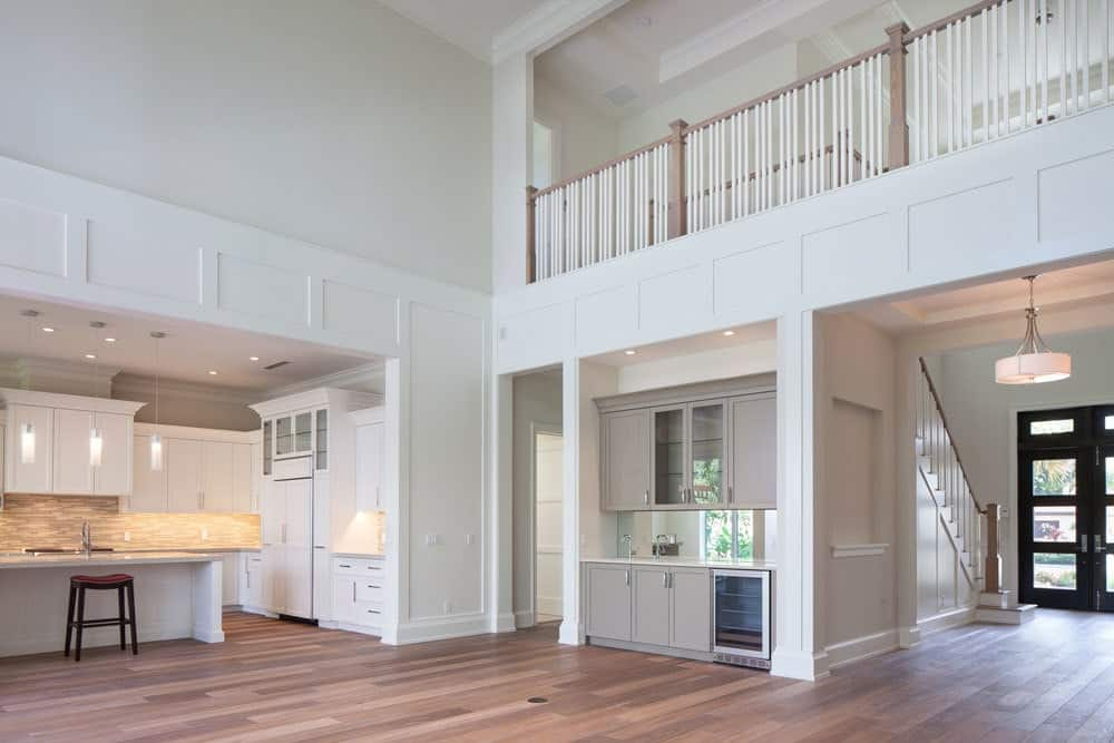 Spacious living room with hardwood flooring, soaring ceiling, and a bar.
