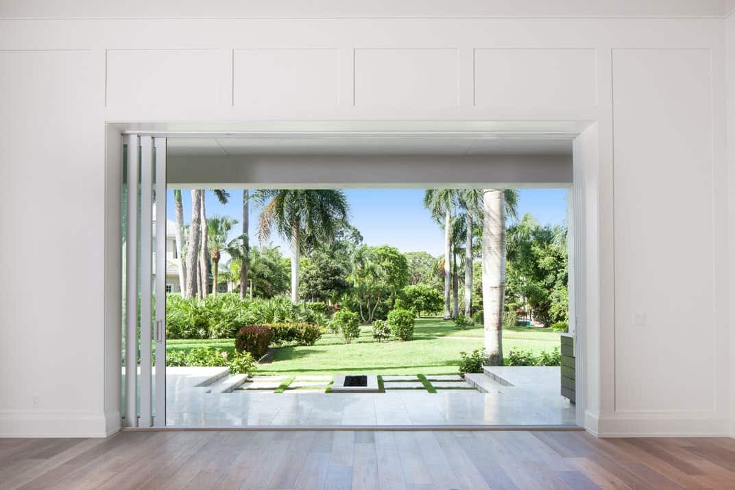 View of the backyard from the living room showing its expansive lawn and lush greenery.