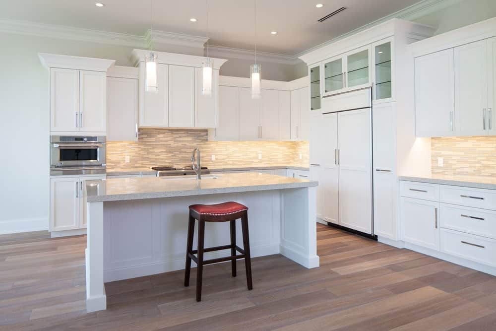 Kitchen with white cabinetry, granite countertops, linear mosaic tile backsplash, and breakfast island.