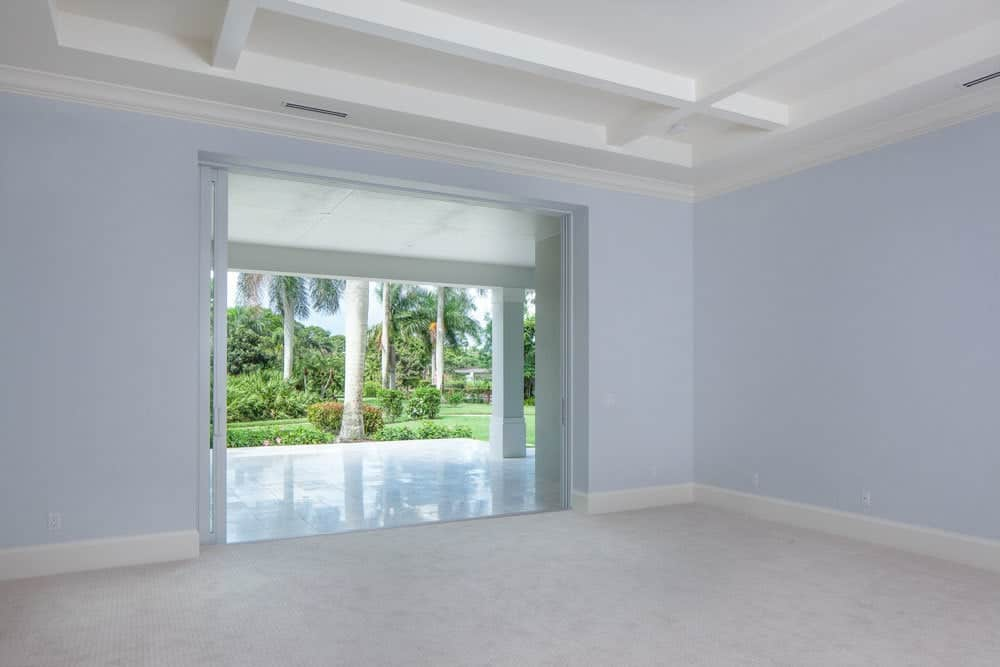 Primary bedroom with a tray ceiling, light blue walls, sliding glass doors that open to the covered lanai.