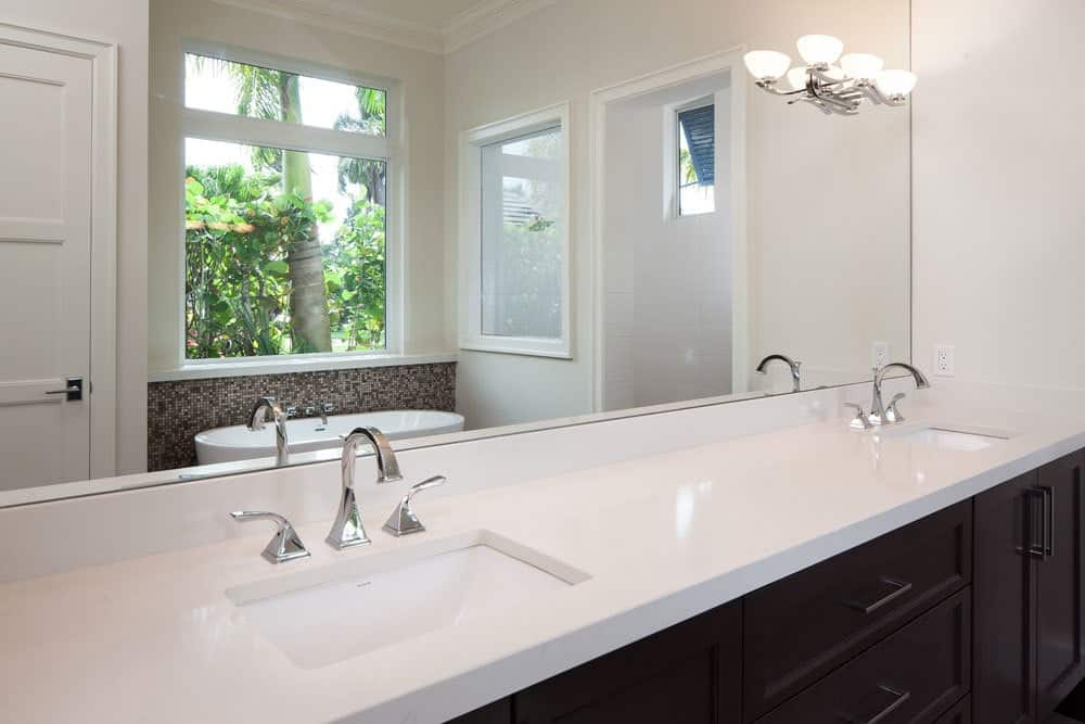 Black vanity with double sinks and a large frameless mirror mounted with chrome sconces.