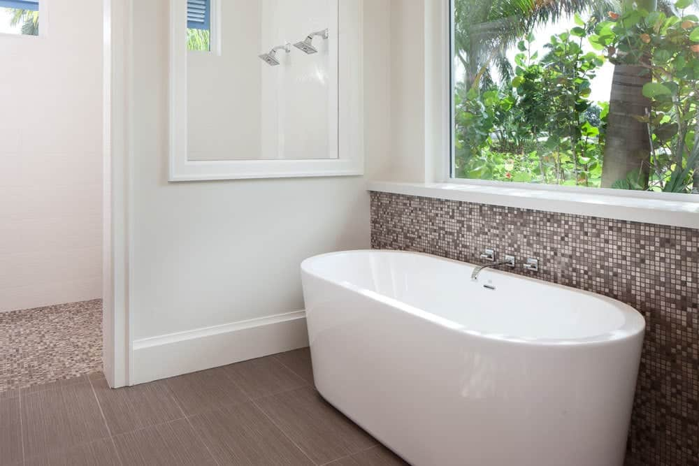 Primary bedroom with a walk-in shower and a freestanding tub placed against the mosaic tile backsplash.