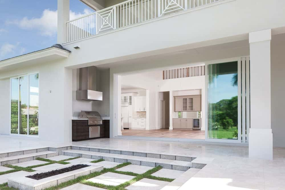 Rear patio with marble flooring, a summer kitchen, and a fire pit.