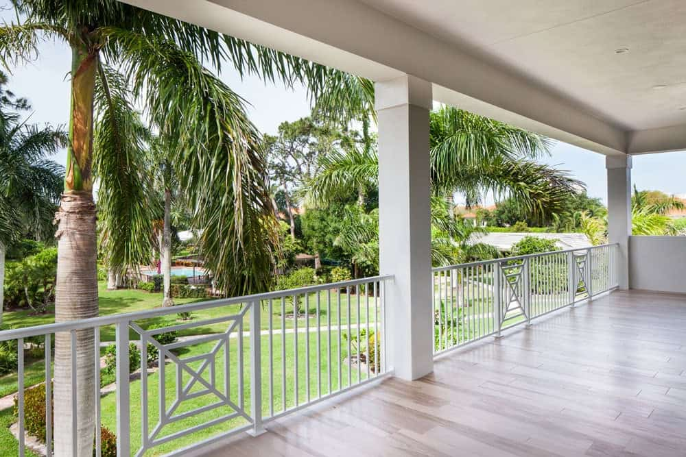 Spacious balcony with wide plank flooring, gray columns, and decorative white railings.