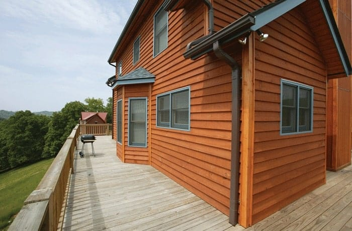 A closer look at the wrap-around porch showing its wide plank flooring and wooden railings.