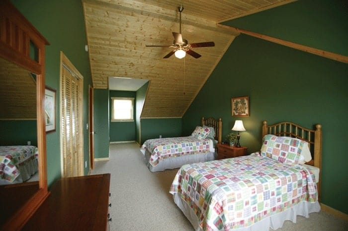 Bedroom with vaulted ceiling, green walls, carpet flooring, and two beds.
