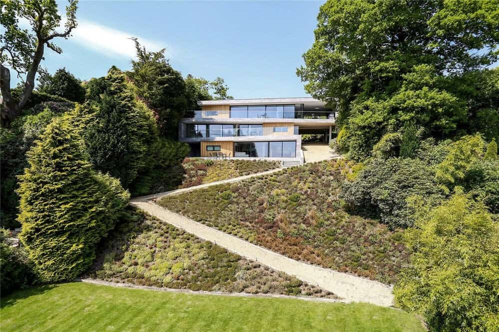 This is far-off view of the whole house and its surrounding landscape with tall trees on both sides and a winding walkway up a hill to the house.