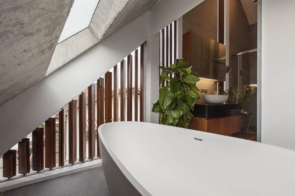 The bathroom has a freestanding bathtub illuminated by the skylight on the low shed ceiling.