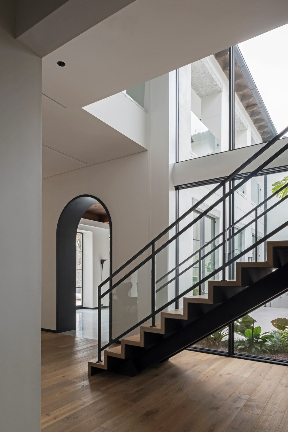 This is a closer look at the staircase that has black elements illuminated by the large glass wall that spans two floors giving a view of the patio outside.