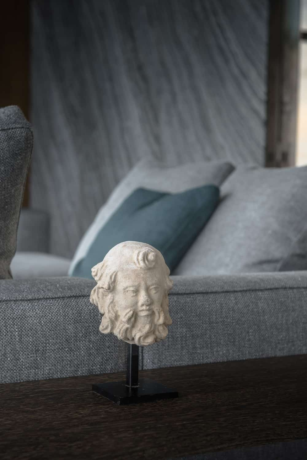 This is a close look at the white figurine on the console table behind the gray sectional sofa.
