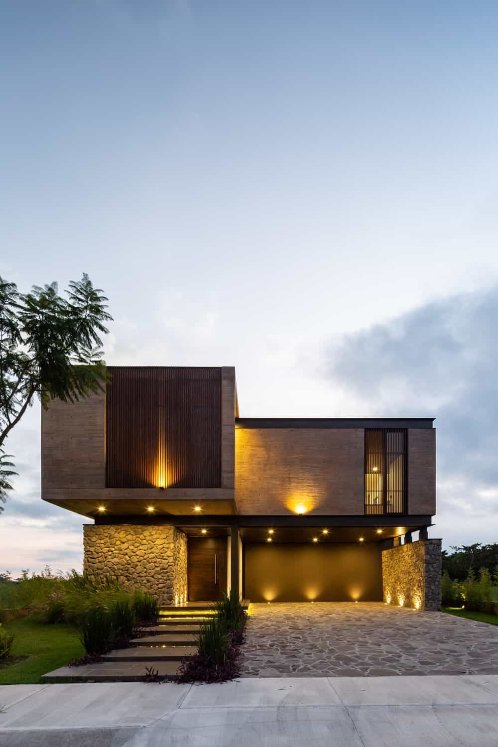 The stone walls are topped with concrete structures that are complemented by thin slat panels that glow warmly with the exterior lights.